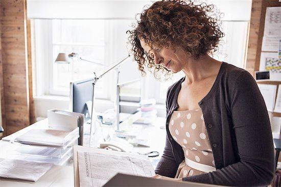 Businesswoman reading folder in office Stock Photo - Premium Royalty-Free, Image code: 614-08869345
