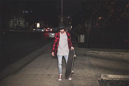 Male hipster skateboarder walking along sidewalk at night Stock Photo - Premium Royalty-Free, Image code: 614-08877269