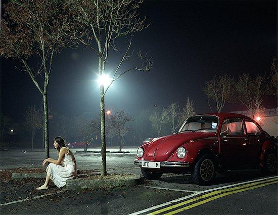 Woman sitting in car park at night Stock Photo - Premium Royalty-Free, Image code: 614-08872814