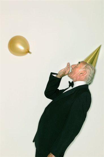Senior man inflating a balloon Stock Photo - Premium Royalty-Free, Image code: 614-00599151