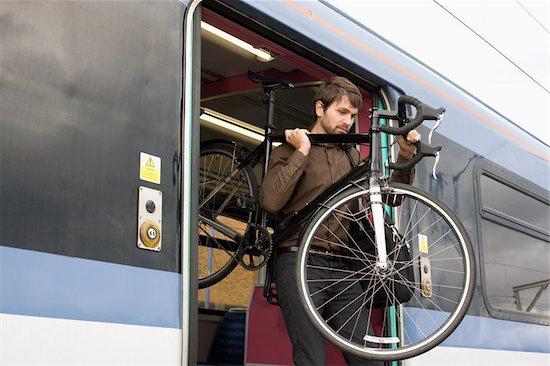 Man with bike on train Stock Photo - Premium Royalty-Free, Image code: 614-02679477