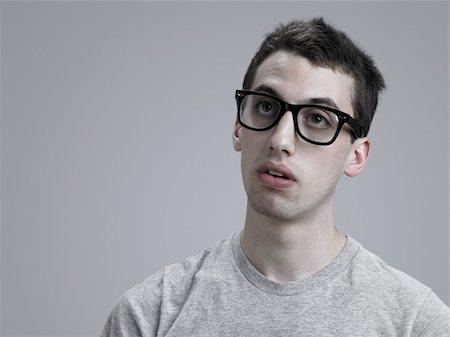 7567b729f738 dorky guy - Young man wearing glasses Stock Photo - Premium Royalty-Free