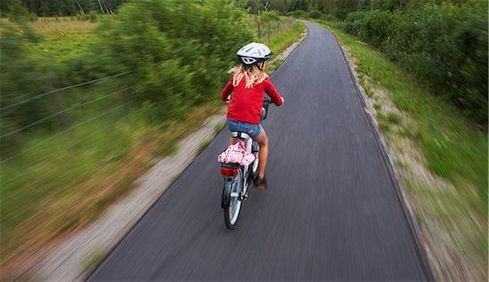 Girl riding bike Stock Photo - Premium Royalty-Free, Image code: 6102-05603746