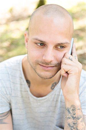 04e8e666a8697 front bald head tattoos - Mid adult man talking via cell phone Stock Photo  - Premium