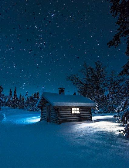 Illuminated log house at night Stock Photo - Premium Royalty-Free, Image code: 6102-08063002