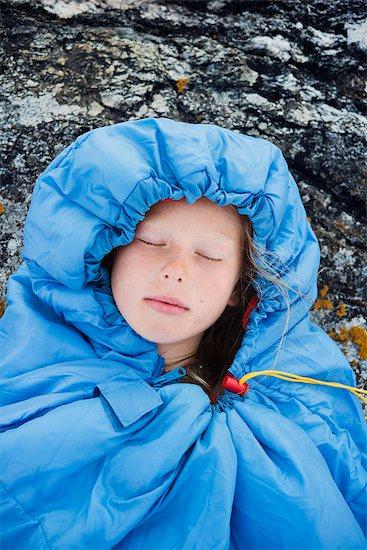 Girl sleeping in sleeping bag on rocks Stock Photo - Premium Royalty-Free, Image code: 6102-08000539