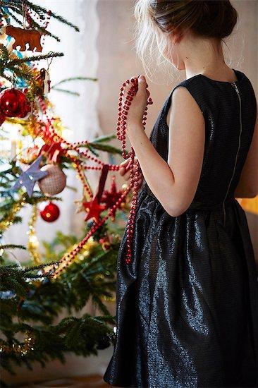 Girl decorating Christmas tree Stock Photo - Premium Royalty-Free, Image code: 6102-08480847
