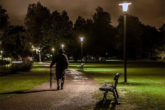 Man walking through park at night, Ronneby, Blekinge, Sweden Stock Photo - Premium Royalty-Free, Image code: 6102-08559288