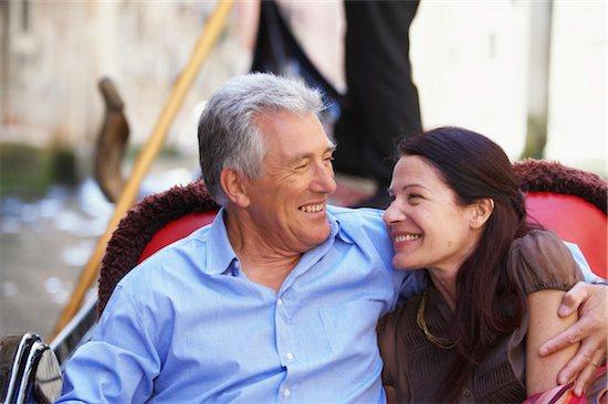 Italy, Venice, mature couple sitting in gondola, smiling, close-up Stock Photo - Premium Royalty-Free, Image code: 6106-05543275