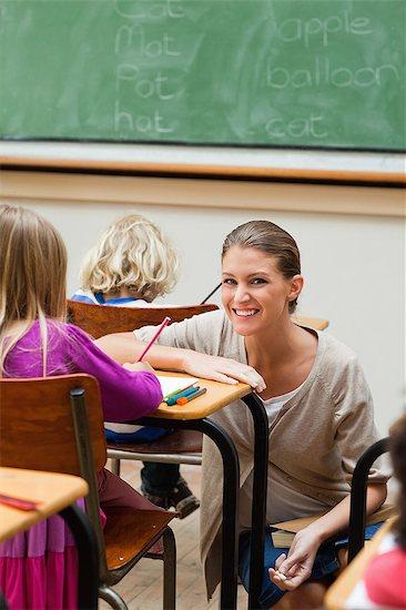 Smiling teacher kneeling next to students desk Stock Photo - Premium Royalty-Free, Image code: 6109-06196451