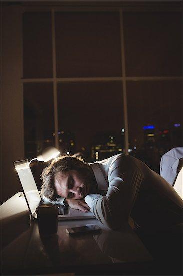 Businessman sleeping on his laptop at night Stock Photo - Premium Royalty-Free, Image code: 6109-08581421