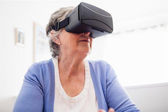 Senior woman using an oculus rift Stock Photo - Premium Royalty-Free, Image code: 6109-08538204