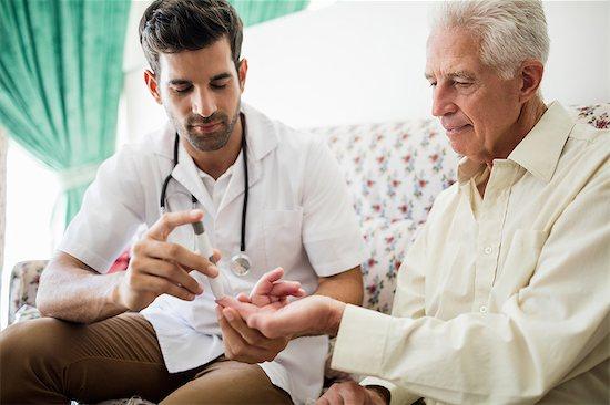 Nurse testing blood glucose of a senior man Stock Photo - Premium Royalty-Free, Image code: 6109-08538378