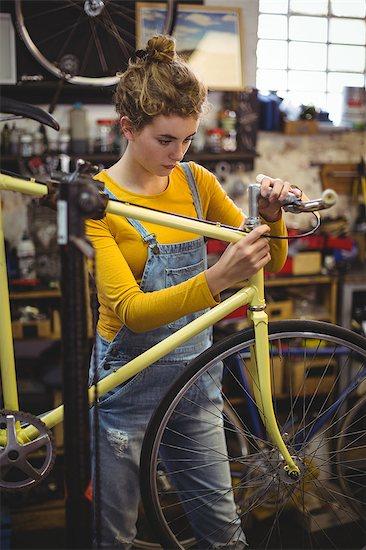 Mechanic repairing a bicycle handle bar in bicycle workshop Stock Photo - Premium Royalty-Free, Image code: 6109-08782899