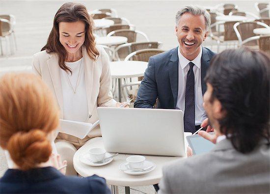 Laughing business people meeting at sidewalk cafe Stock Photo - Premium Royalty-Free, Image code: 6113-06498267