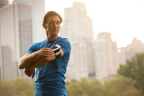 Runner stretching in urban park Stock Photo - Premium Royalty-Free, Image code: 6113-06720355