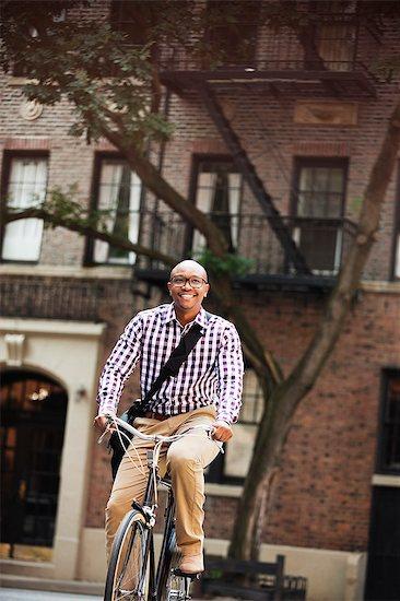 Man riding bicycle on city street Stock Photo - Premium Royalty-Free, Image code: 6113-06720451