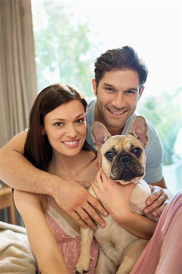 Couple hugging dog on bed Stock Photo - Premium Royalty-Free, Image code: 6113-06720882