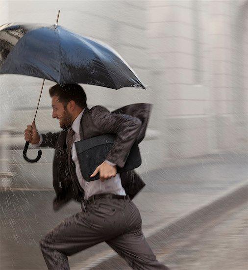 Businessman with umbrella running in rain Stock Photo - Premium Royalty-Free, Image code: 6113-06899540