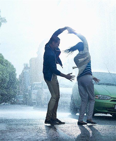 Happy couple dancing in rain Stock Photo - Premium Royalty-Free, Image code: 6113-06899584
