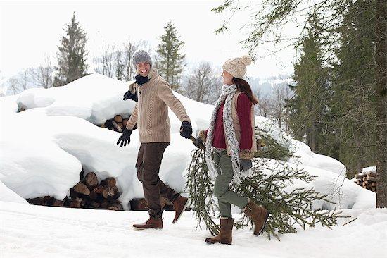 Couple dragging fresh Christmas tree near snow covered woodpile Stock Photo - Premium Royalty-Free, Image code: 6113-06899506