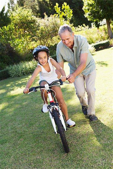 Older man teaching granddaughter to ride bicycle Stock Photo - Premium Royalty-Free, Image code: 6113-06909467