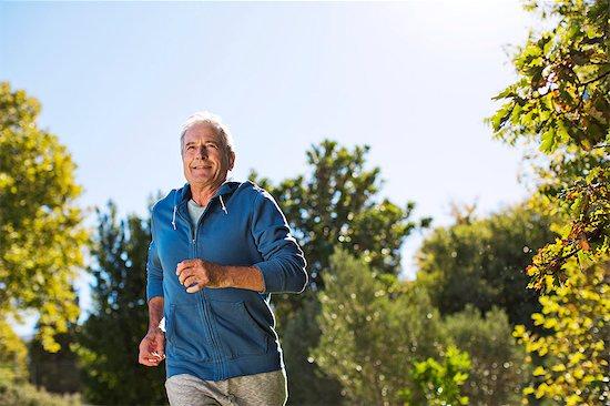 Senior man running in park Stock Photo - Premium Royalty-Free, Image code: 6113-07146892