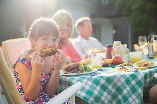 Girl eating corncob at table in backyard Stock Photo - Premium Royalty-Free, Image code: 6113-07242431