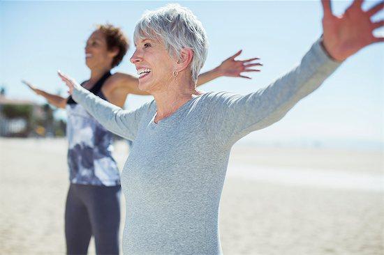 Senior women stretching arms on beach Stock Photo - Premium Royalty-Free, Image code: 6113-07589370