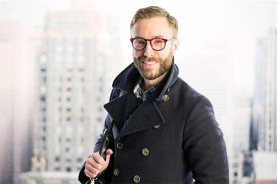 Portrait of smiling businessman in urban window Stock Photo - Premium Royalty-Free, Image code: 6113-07648727