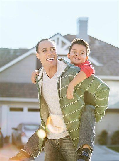 Father piggybacking son Stock Photo - Premium Royalty-Free, Image code: 6113-07648814