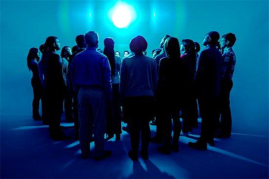 Crowd standing around bright light Stock Photo - Premium Royalty-Free, Image code: 6113-07730649