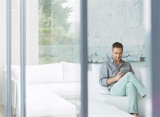 Man using digital tablet on sofa Stock Photo - Premium Royalty-Free, Image code: 6113-07730763