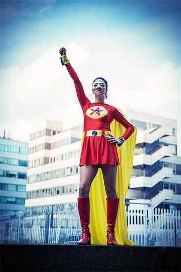 Superhero standing proudly in city Stock Photo - Premium Royalty-Free, Image code: 6113-07961751