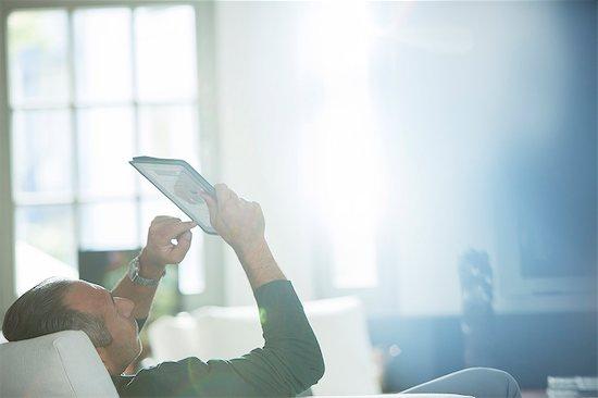 Older man using digital tablet on sofa Stock Photo - Premium Royalty-Free, Image code: 6113-07906141