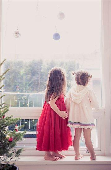 Girls on window ledge below Christmas ornaments Stock Photo - Premium Royalty-Free, Image code: 6113-08088520