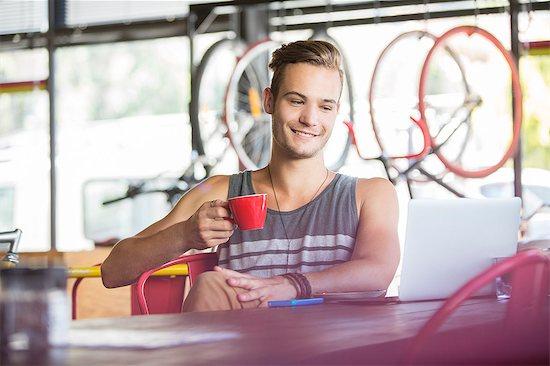 Smiling man drinking coffee at laptop in bike shop Stock Photo - Premium Royalty-Free, Image code: 6113-08171259