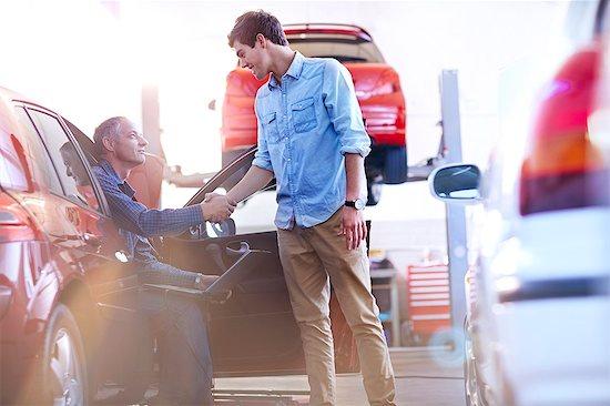 Mechanic and customer handshaking in auto repair shop Stock Photo - Premium Royalty-Free, Image code: 6113-08184340
