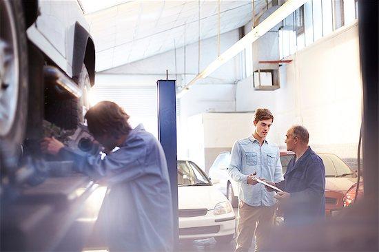 Mechanic speaking with customer in auto repair shop Stock Photo - Premium Royalty-Free, Image code: 6113-08184342