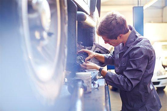 Mechanic examining part in auto repair shop Stock Photo - Premium Royalty-Free, Image code: 6113-08184351