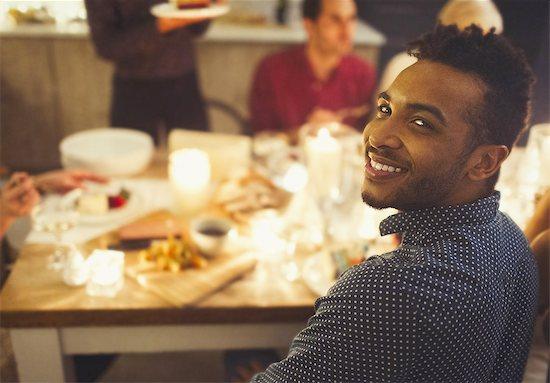 Portrait smiling man enjoying candlelight Christmas dinner Stock Photo - Premium Royalty-Free, Image code: 6113-08659570