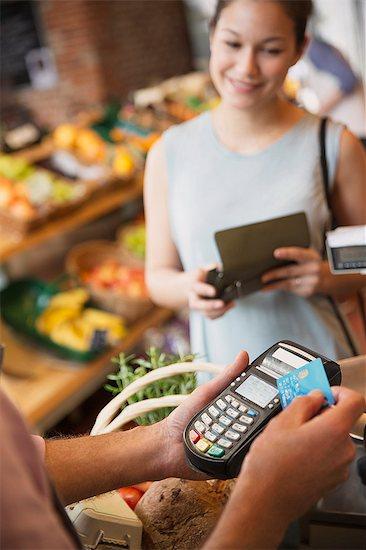 Woman watching grocery store clerk using credit card machine Stock Photo - Premium Royalty-Free, Image code: 6113-08722170