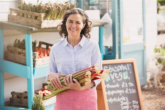 Portrait smiling farmer's market worker holding fresh rhubarb Stock Photo - Premium Royalty-Free, Image code: 6113-08722171