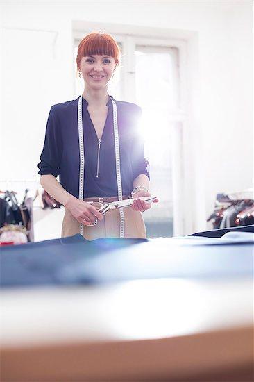 Portrait confident female tailor holding scissors in menswear workshop Stock Photo - Premium Royalty-Free, Image code: 6113-08722302