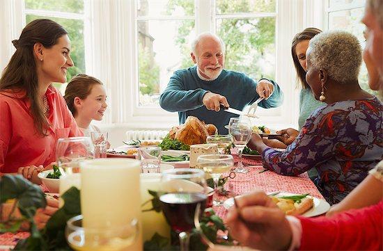 Multi-ethnic family enjoying Christmas dinner table Stock Photo - Premium Royalty-Free, Image code: 6113-08805627