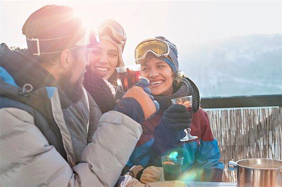 Smiling skier friends drinking cocktails apres-ski Stock Photo - Premium Royalty-Free, Image code: 6113-08947394