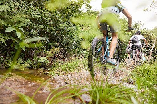 Man mountain biking, splashing on muddy trail Stock Photo - Premium Royalty-Free, Image code: 6113-09168862