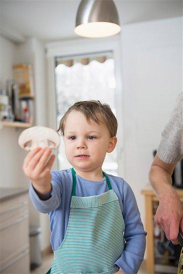 Boy holding mushroom slice in kitchen Stock Photo - Premium Royalty-Free, Image code: 6121-07740157