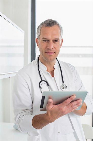 Doctor holding digital tablet, portrait Stock Photo - Premium Royalty-Free, Image code: 6121-07741207