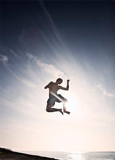 Teenage boy posing in mid-air Stock Photo - Premium Royalty-Free, Image code: 6122-07706002